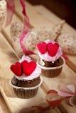 Magdalenas con crema y corazones rojos Fotografía de archivo