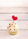 Magdalenas con los corazones rojos para el día de tarjetas del día de San Valentín del St Fondo de madera blanco foto de archivo