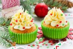 Magdalenas de la Navidad con helar del buttercream y confeti del azúcar Fotografía de archivo libre de regalías