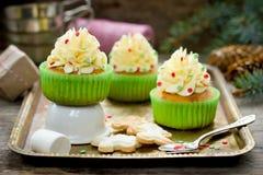 Magdalenas de la Navidad con helar del buttercream y confeti del azúcar Foto de archivo