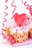 Magdalenas de la tarjeta del día de San Valentín con el corazón del caramelo Fotos de archivo