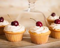 Magdalenas de la vainilla con helar poner crema de la mantequilla y una cereza en el top Imagen de archivo