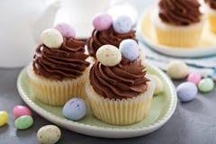 Magdalenas de la vainilla de Pascua con helar del chocolate Imagen de archivo libre de regalías