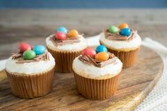 Magdalenas de Pascua con helar del chocolate y huevos de caramelo Imagenes de archivo