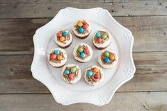 Magdalenas de Pascua con helar del chocolate y huevos de caramelo Imágenes de archivo libres de regalías