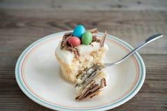 Magdalenas de Pascua con helar del chocolate y huevos de caramelo Foto de archivo libre de regalías