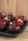 Magdalenas del chocolate adornadas con crema del chocolate y azufaifas del verano Fotos de archivo libres de regalías