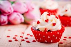 Magdalenas del chocolate con crema de la vainilla y corazones rojos del azúcar para el día de tarjeta del día de San Valentín fotos de archivo libres de regalías