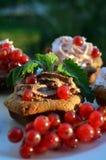 Magdalenas del chocolate con crema y bayas Imagen de archivo libre de regalías