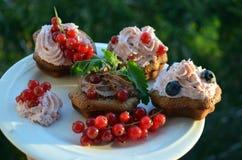 Magdalenas del chocolate con crema y bayas Imagen de archivo