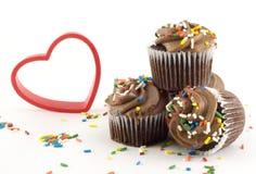 Magdalenas del chocolate con el corazón rojo fotos de archivo