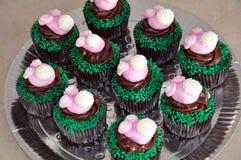 Magdalenas del chocolate con los conejitos de pascua rosados Fotografía de archivo libre de regalías