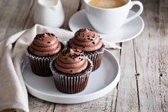 Magdalenas del chocolate con una taza de café Imagenes de archivo