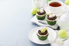 Magdalenas del chocolate de Pascua con los huevos de la jerarquía y de caramelo para el postre foto de archivo