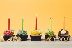 Magdalenas del chocolate en fila con las velas Fotos de archivo libres de regalías
