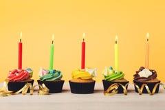 Magdalenas del chocolate en fila con las velas Fotografía de archivo