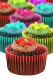 Magdalenas del chocolate en tazas coloridas Foto de archivo libre de regalías