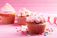 Magdalenas del cumpleaños con crema de la mantequilla en fondo colorido Imagenes de archivo