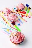 Magdalenas del cumpleaños con el remolino poner crema azotado rosado, vertical Imagen de archivo