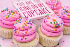 Magdalenas del cumpleaños con helar rosado Foto de archivo