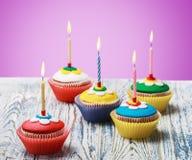 Magdalenas del cumpleaños con las velas ardientes Imágenes de archivo libres de regalías
