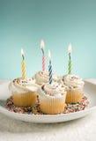 Magdalenas del cumpleaños con las velas coloreadas Foto de archivo libre de regalías