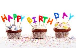 Magdalenas del cumpleaños con las velas coloridas Foto de archivo libre de regalías