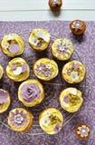 Magdalenas delicadas de la vainilla en fondo floral Foto de archivo libre de regalías