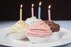 Magdalenas en colores pastel con las velas del cumpleaños en la placa Imagen de archivo