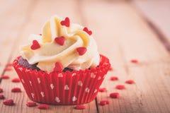 Magdalenas hechas en casa de la tarjeta del día de San Valentín con los corazones rojos del azúcar Fotografía de archivo