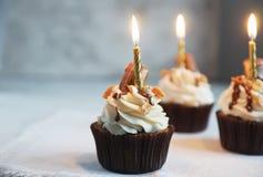 Magdalenas hechas en casa del chocolate con helar de la vainilla, adornado con las nueces y las velas fotos de archivo