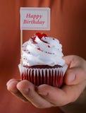 Magdalenas rojas festivas del terciopelo con una tarjeta del cumplido Imagen de archivo libre de regalías