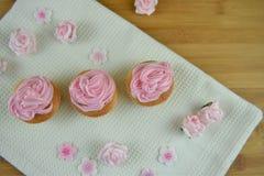 Magdalenas rosadas hermosas con las flores heladas para un regalo del día de madres Fotos de archivo libres de regalías