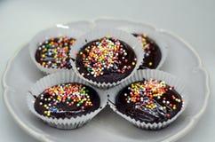 Magdalenas sabrosas del chocolate del cumpleaños con el chocolate y los caramelos en el top Imagen de archivo libre de regalías