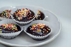 Magdalenas sabrosas del chocolate del cumpleaños con el chocolate y los caramelos en el top Fotografía de archivo