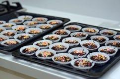 Magdalenas sabrosas del chocolate del cumpleaños con el chocolate y los caramelos en el top Fotos de archivo