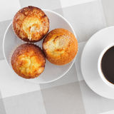 Magdalenas, typical spanish plain muffins, and cof. A plate with some magdalenas, typical spanish plain muffins, and a cup of coffee on a set table Royalty Free Stock Photography