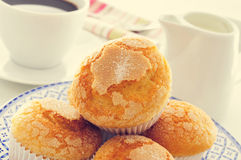Magdalenas, typical spanish plain muffins, and coffee. Closeup a plate with some magdalenas, the typical spanish plain muffins, on a set table with a cup of Stock Photography