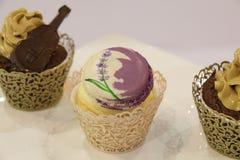 Magdalenas: vainilla, chocolate, en tazas decorativas Foto de archivo