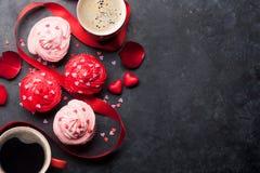 Magdalenas y tazas de café deliciosas fotografía de archivo