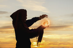 Mage Creating a Fireball. A magician woman is summoning a fireball at sunset royalty free stock photography