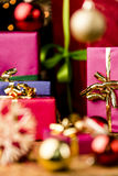 Magenta and Blue Gifts amidst Golden Glitter. Christmas presents in solid colors between baubles and straw stars. Focus is on the golden bow knot around the Royalty Free Stock Image
