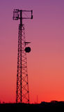 Magenta Cell Phone Tower. A cell phone tower silhouette in the sunset Royalty Free Stock Images
