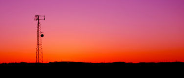 Magenta Cell Phone Tower Panaramic. A cell phone tower silhouette in the sunset Royalty Free Stock Images