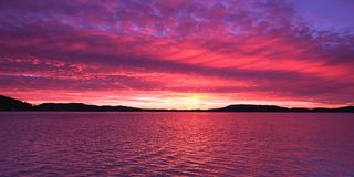 Magenta coloured altostratus cloudy Sunrise Seascape Panorama. A magnificient panoramic inspirational magenta coloured altostratus cloudy sunrise seascape over stock photo