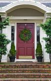 Magenta Door with Wreath. On gray home with mossy red brick steps Stock Image