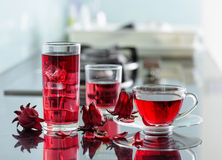 Magenta hibiscus tea (karkade, red sorrel) on kitchen table. Cup of hot hibiscus tea (karkade, red sorrel, Agua de flor de Jamaica) and the same cold drink with Royalty Free Stock Image
