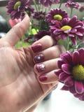 Magenta nails. Art flowers manicure magenta black polish painted fingers stock photography