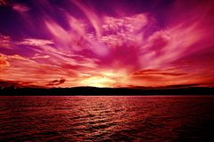 Magenta rays Ocean Sunset. Australia. Spectacular vivid pink magenta cirrus cloudy Ocean Sunset with water reflections...Photographed in Lake Macquarie, NSW stock photography