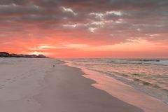 Magenta Sunrise with Buildings and Birds on Florida Coastline. Sunrise on Florida coast with magenta and orange tones and emerald green water Stock Images